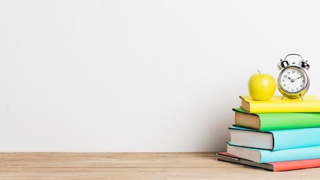 Despertador y manzana amarilla en pila de libros
