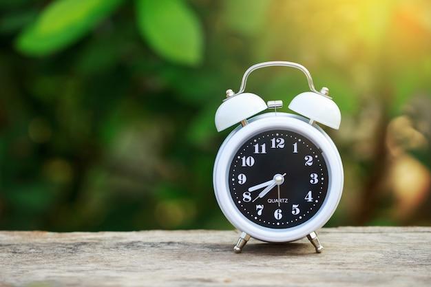 Despertador en la mesa con desenfoque hojas verdes fondo y rayo de sol