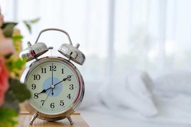 Despertador en la mesa en el dormitorio con copyspace