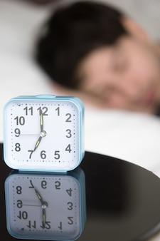 Despertador en mesa frente a hombre dormido, vertical.
