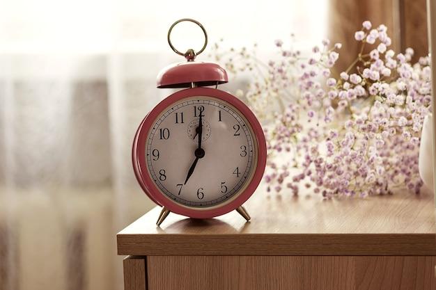 El despertador está en la mesa junto a la cama, al lado de las flores, a la hora de despertarse por la mañana.