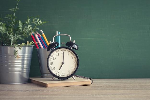 Despertador en mesa de madera sobre fondo de pizarra en el aula