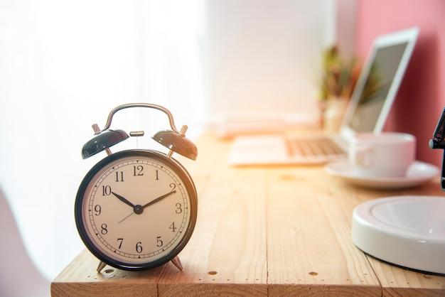 Despertador en la mesa de trabajo fecha límite de negocios con taza de café y computadora portátil