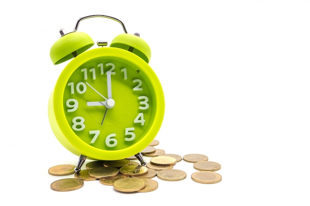Despertador con monedas aisladas en blanco