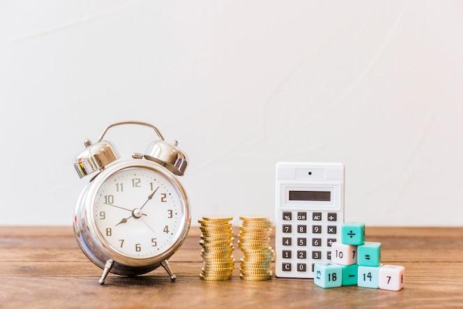 Despertador, monedas apiladas, calculadora y bloques de matemáticas en el escritorio de madera