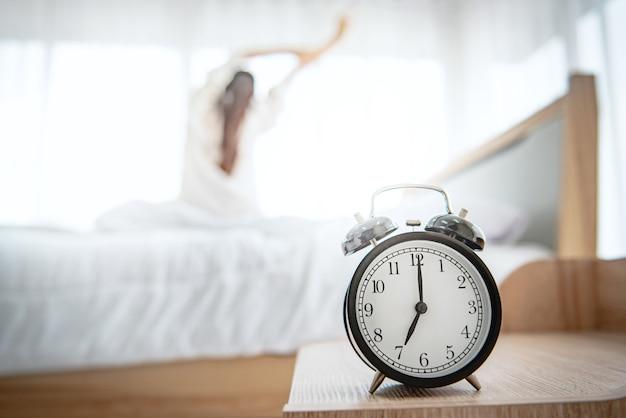 Despertador con mujer feliz que se extiende en la cama después de despertarse.
