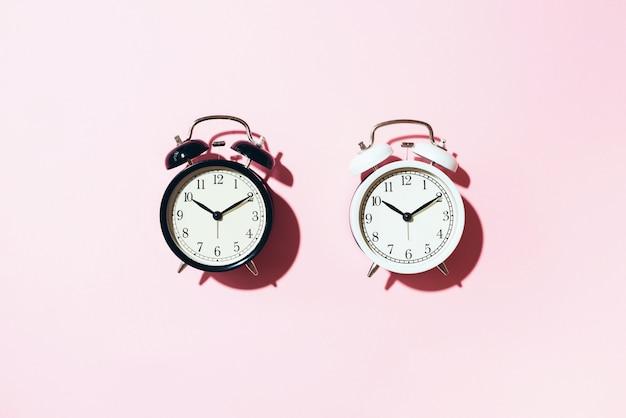 Despertador negro y blanco con sombra dura sobre fondo rosa.