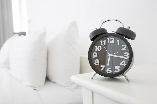 Despertador negro y cama