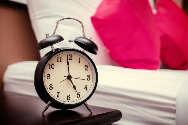 Despertador negro en el dormitorio y almohadas rojas.