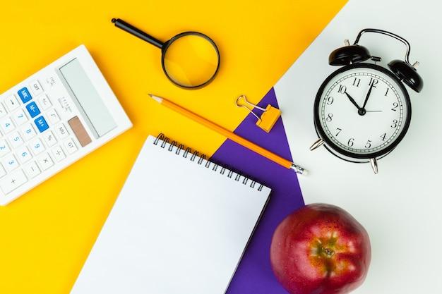 Despertador negro, papelería, bloc de notas, calculadora, útiles de oficina