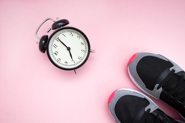 Despertador negro retro y negro con zapatillas de frambuesa sobre un fondo rosa.