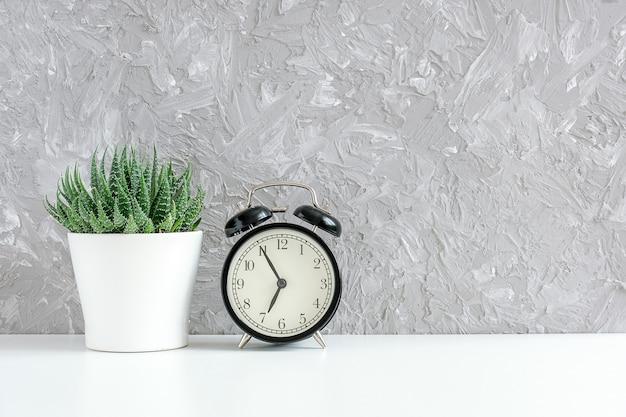 Despertador negro y verde suculento en maceta blanca sobre mesa, muro de hormigón gris.