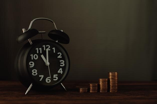 Despertador y paso de pilas de monedas en la mesa de trabajo