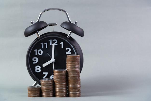 Despertador y paso de pilas de monedas en mesa de trabajo.
