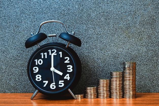 El despertador y el paso de las pilas de las monedas en la tabla de funcionamiento, hora para el concepto del dinero de los ahorros.