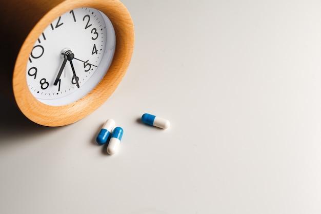 Despertador y pastillas blancas sobre mesa blanca
