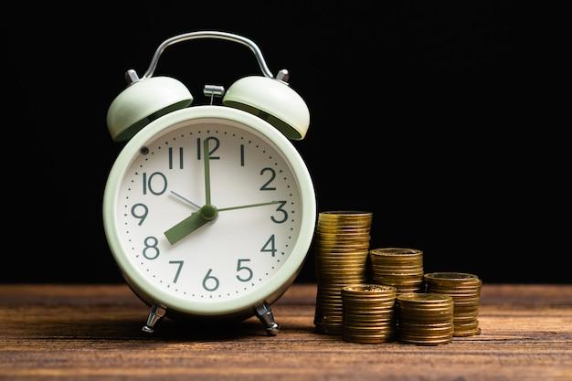 Despertador y pilas de monedas en mesa de trabajo en cuarto oscuro