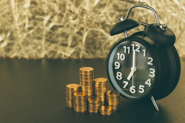 Despertador y pilas de monedas en la mesa de trabajo