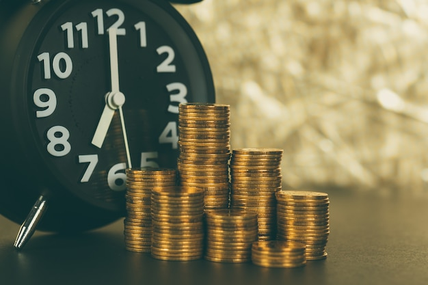 Despertador y pilas de monedas en mesa de trabajo