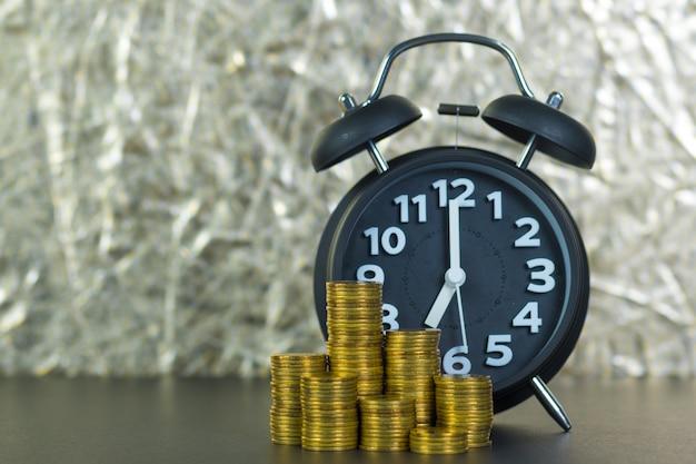 Despertador y pilas de monedas en la mesa