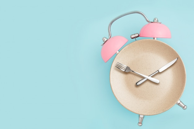 Despertador y plato con cubiertos. concepto de ayuno intermitente, almuerzo, dieta y pérdida de peso.