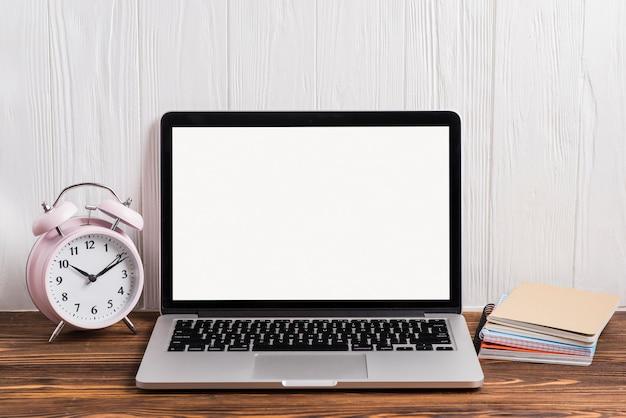 Despertador; un portátil abierto y un cuaderno apilados en el escritorio de madera contra la pared