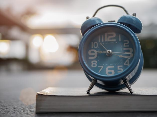 Despertador del primer en el libro con el fondo de la puesta del sol.