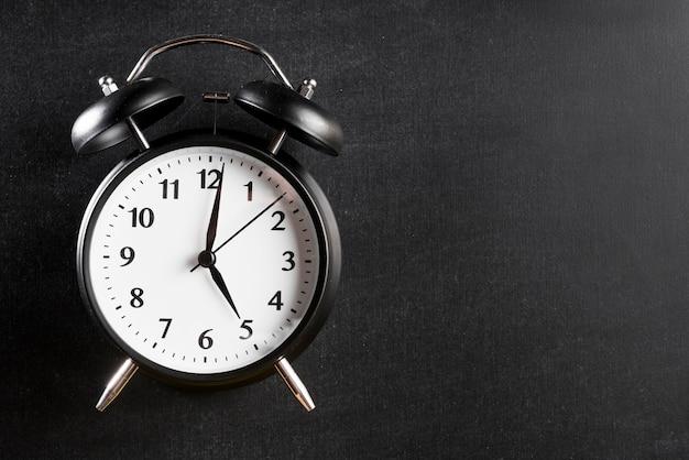 Despertador que muestra 5'o reloj contra fondo negro