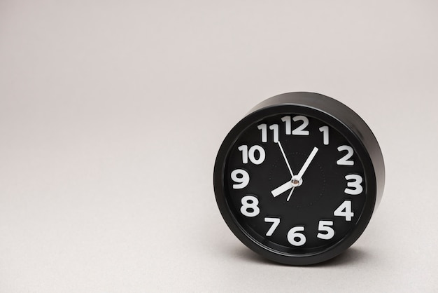 Despertador redondo negro contra fondo gris