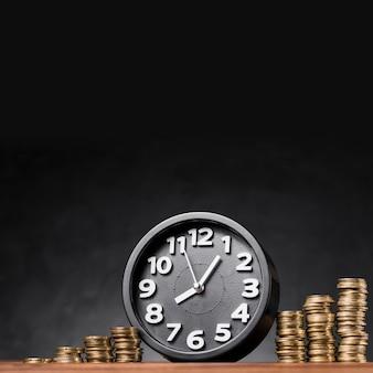 Despertador redondo negro entre la pila de monedas de oro sobre fondo negro