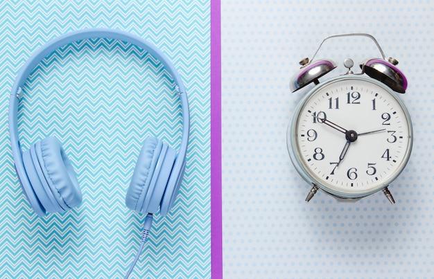 Despertador retro y auriculares sobre fondo creativo.