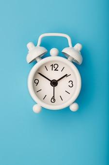 Despertador retro blanco sobre fondo azul. concepto de tiempo con espacio libre para texto.