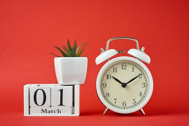 Despertador retro blanco sobre fondo rojo y bloques de calendario de madera