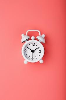 Despertador retro blanco sobre fondo rosa. concepto de tiempo con espacio libre para texto.