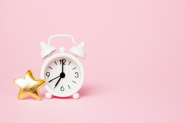 Despertador retro con decoracion de fiesta sobre fondo rosa