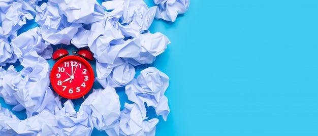 Despertador rojo con bolas de papel arrugado blanco sobre un fondo azul.