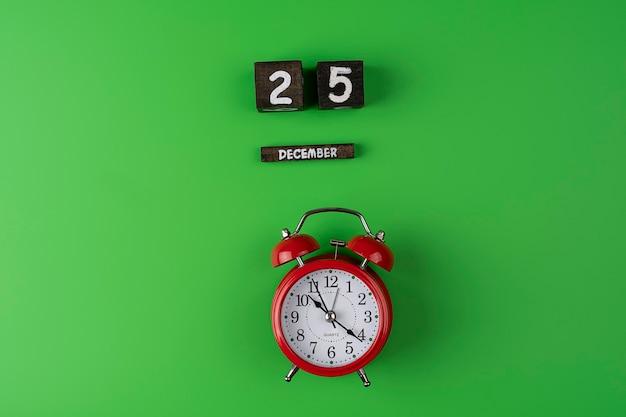 Despertador rojo en el centro del fondo verde con fecha del 25 de diciembre celebrar