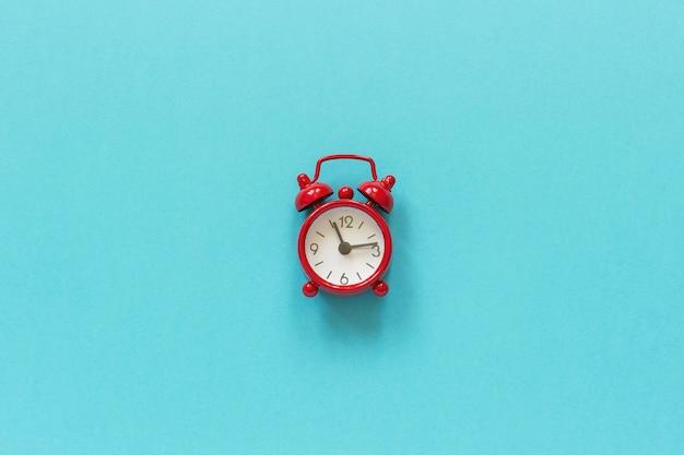 Despertador rojo en el centro sobre fondo de papel azul.