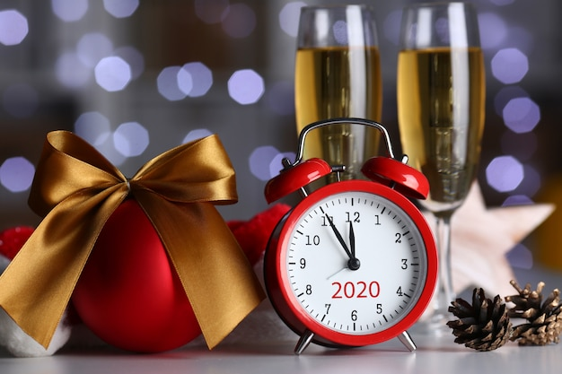 Despertador rojo y copa de champán en la mesa de oficina