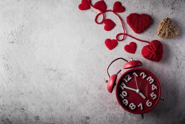 Despertador rojo con el corazón rojo, concepto del día de tarjetas del día de san valentín.