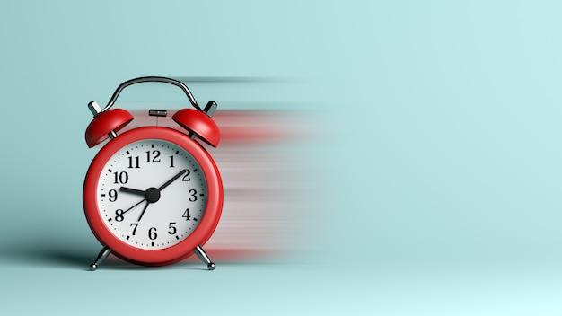 Despertador rojo con efecto de desenfoque sobre fondo azul.