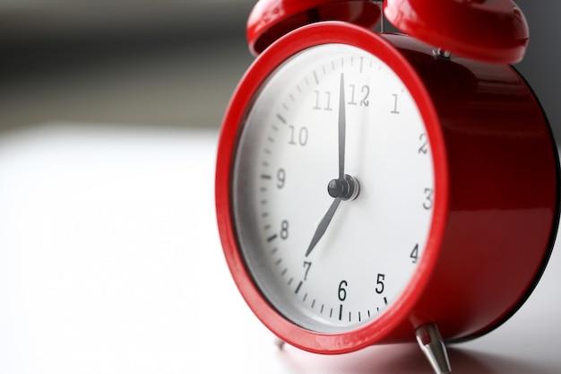 Despertador rojo fijado a las siete de la mañana