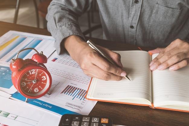 Despertador rojo con el hombre de negocios que trabaja antes de la fecha límite, concepto de gestión de tiempo.
