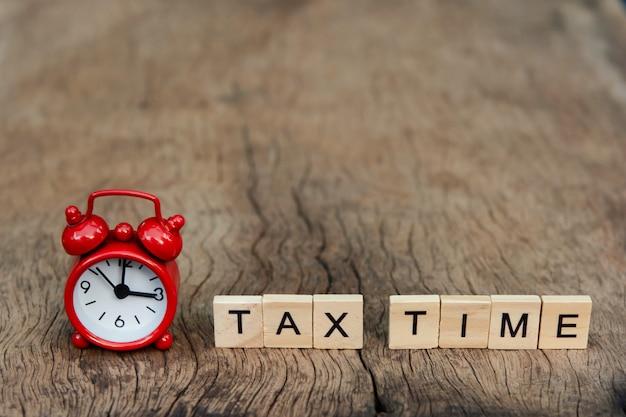 Despertador rojo y hora de impuestos con bloques de madera del alfabeto