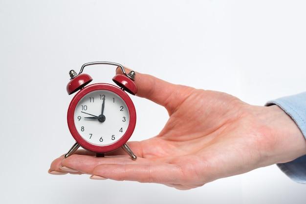 Despertador rojo en una mano femenina sobre un fondo blanco.