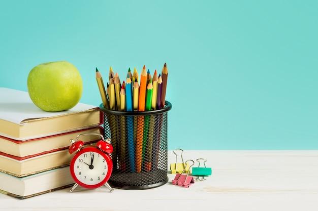 Despertador rojo, manzana, lápices de colores, libros sobre un fondo azul.