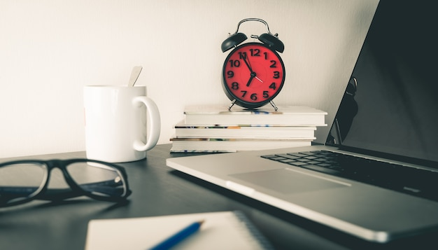 Despertador rojo en mesa de oficina con objetos
