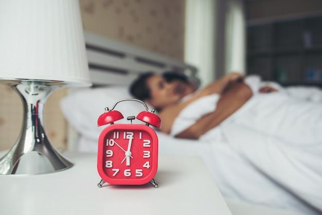 Despertador rojo con pareja durmiendo cómodamente en la cama en casa