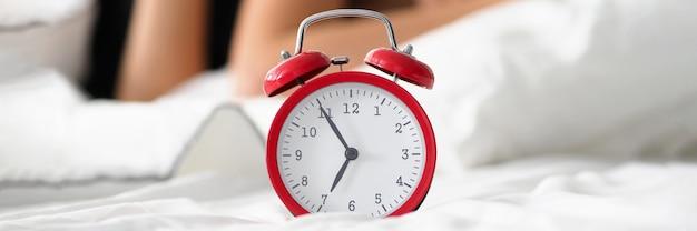 Despertador rojo que muestra cinco antes de las siete
