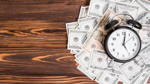 Despertador sobre las notas de la moneda de cien dólares en el fondo con textura de madera